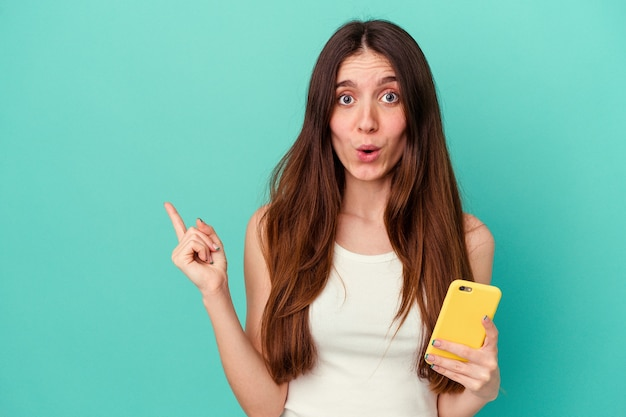 측면을 가리키는 파란색 배경에 고립 된 휴대 전화를 들고 젊은 백인 여자