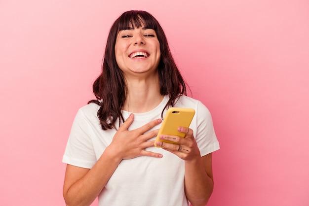 분홍색 배경에 고립 된 휴대 전화를 들고 젊은 백인 여자 큰 소리로 가슴에 손을 유지 웃음.