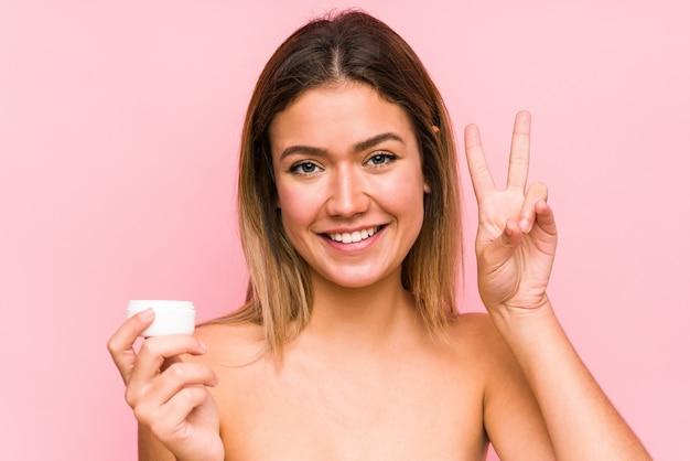 勝利のサインを示すと広く笑みを浮かべて分離された保湿剤を保持している若い白人女性。