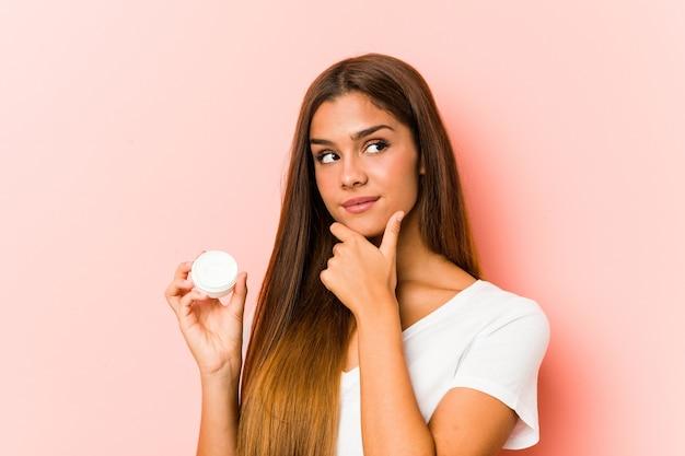 Молодая кавказская женщина, держащая увлажняющий крем, смотрит в сторону с сомнительным и скептическим выражением лица.