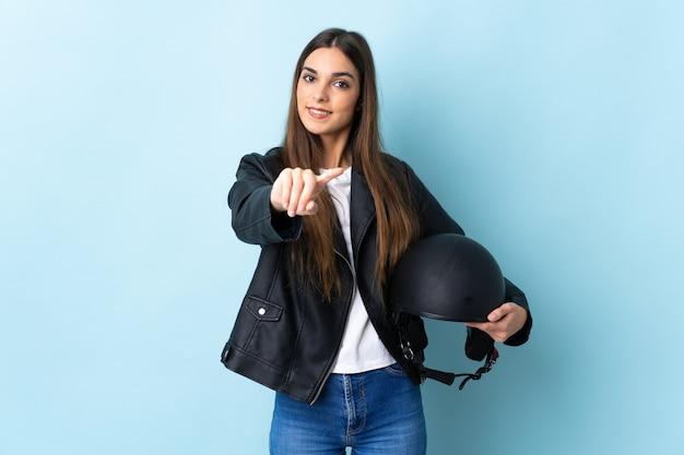 幸せな表情で青いポインティングフロントに分離されたオートバイのヘルメットを保持している若い白人女性