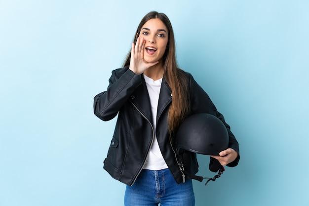 口を大きく開いて叫んで青い壁に分離されたオートバイのヘルメットを保持している若い白人女性