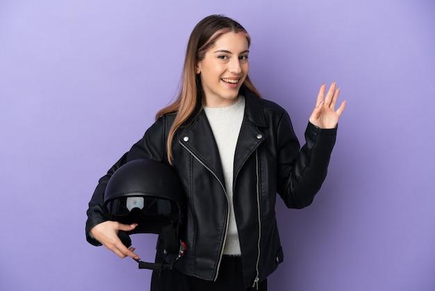 幸せな表情で手で敬礼紫に分離されたオートバイのヘルメットを保持している若い白人女性
