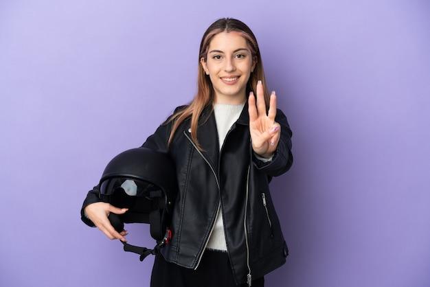 보라색 벽 행복에 고립 된 오토바이 헬멧을 들고 손가락으로 세 세 젊은 백인 여자