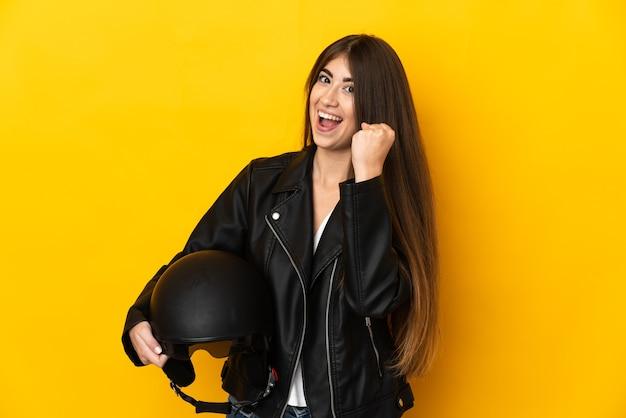 Молодая кавказская женщина, держащая мотоциклетный шлем на желтом фоне, празднует победу