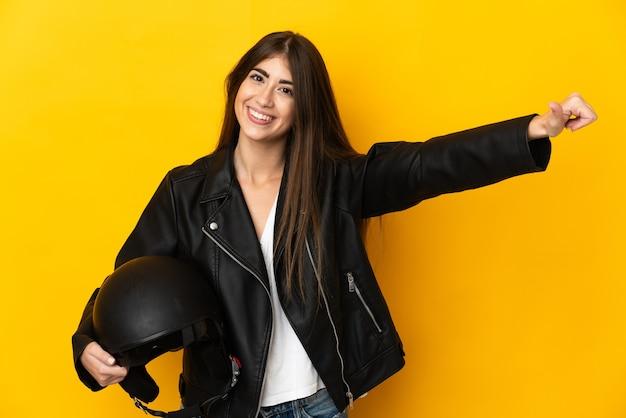 노란색 배경에 격리된 오토바이 헬멧을 들고 엄지손가락을 치켜드는 백인 여성