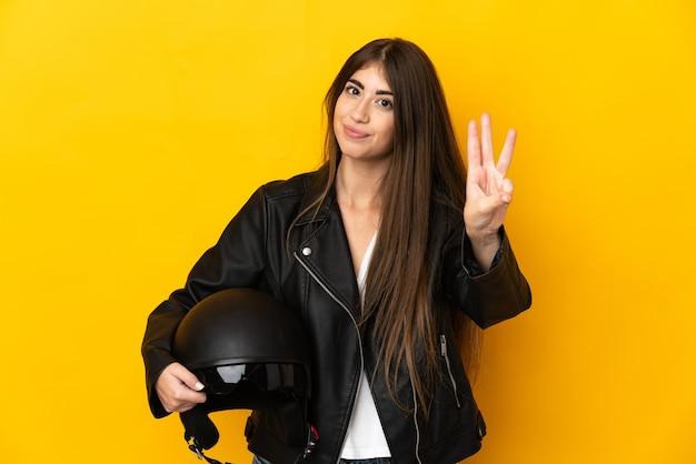 노란색 배경 행복에 고립 된 오토바이 헬멧을 들고 손가락으로 세 세 젊은 백인 여자
