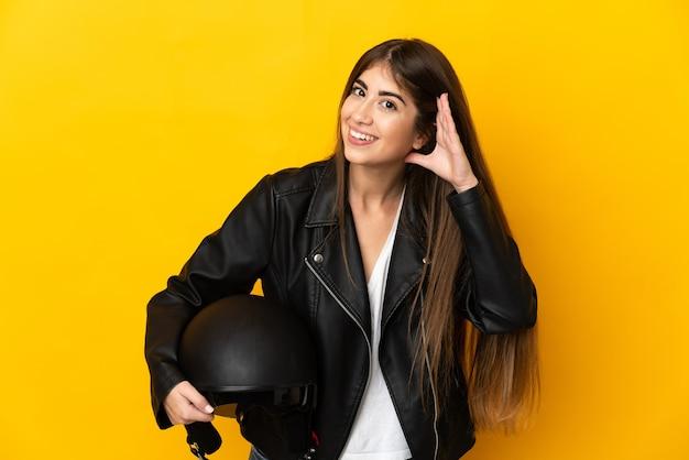 귀에 손을 넣어 뭔가를 듣고 노란색 배경에 고립 된 오토바이 헬멧을 들고 젊은 백인 여자