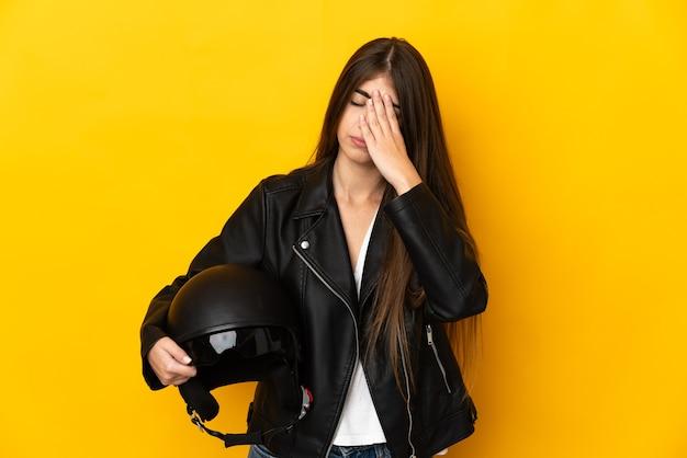 Молодая кавказская женщина, держащая мотоциклетный шлем, изолирована на желтом фоне с усталым и больным выражением лица