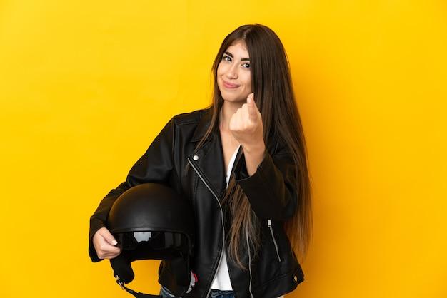 来るジェスチャーをしている黄色の壁に分離されたオートバイのヘルメットを保持している若い白人女性