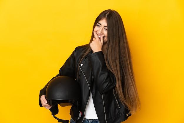 노란색 벽 웃음에 고립 된 오토바이 헬멧을 들고 젊은 백인 여자