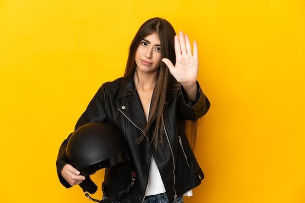 停止ジェスチャーを作る黄色の壁に分離されたオートバイのヘルメットを保持している若い白人女性