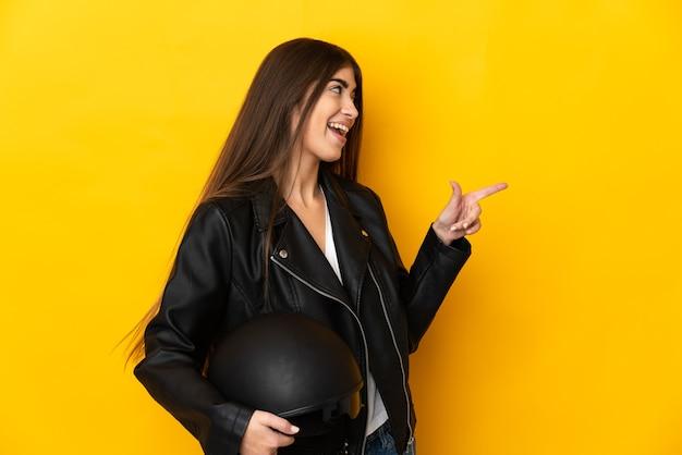 Молодая кавказская женщина, держащая мотоциклетный шлем, изолирована на желтой стене, указывая пальцем в сторону и представляет продукт