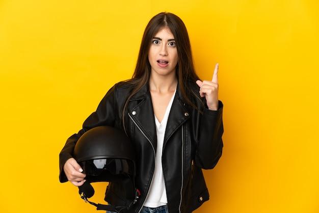 指を上に向けるアイデアを考えて黄色の壁に分離されたオートバイのヘルメットを保持している若い白人女性