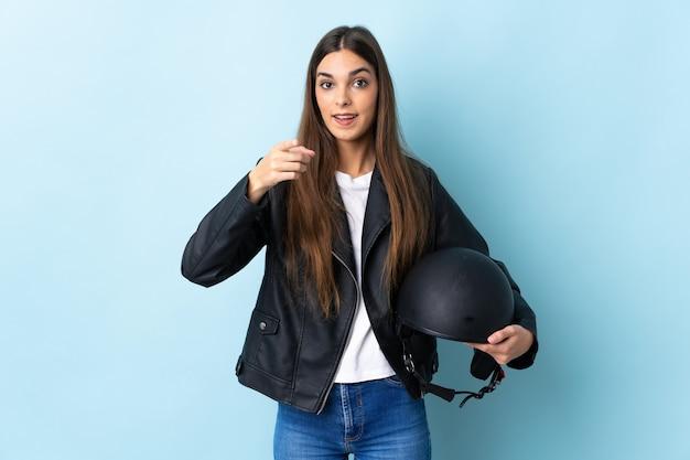 青にオートバイのヘルメットを保持している若い白人女性は驚いて正面を指しています