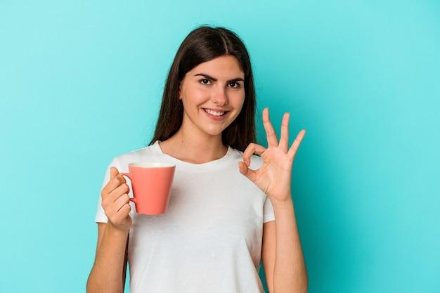 Молодая кавказская женщина, держащая кружку, изолированную на синем фоне, веселая и уверенная, показывая одобренный жест.