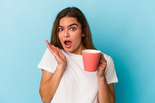 青の背景に分離されたマグカップを保持している若い白人女性は驚き、ショックを受けました。