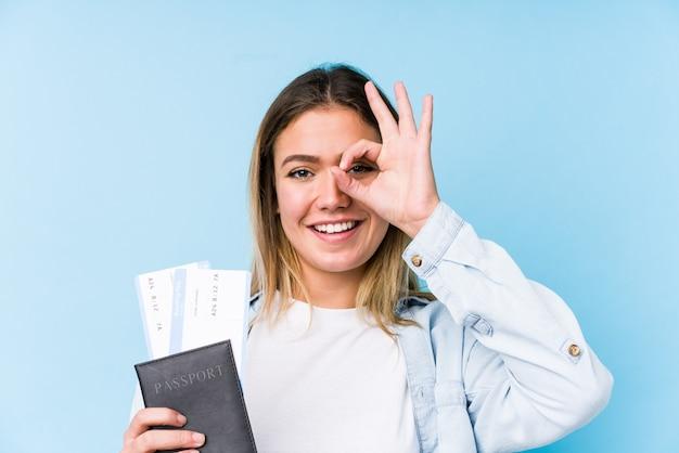 パスポートを保持している若い白人女性は興奮してokのしぐさを目に保持しています。