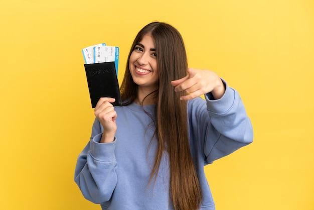 Молодая кавказская женщина, держащая паспорт, изолирована на желтом фоне, указывая вперед с счастливым выражением лица