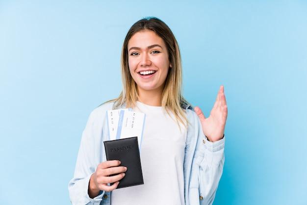 分離されたパスポートを保持している若い白人女性は嬉しい驚きを受けて興奮し、手を上げます。