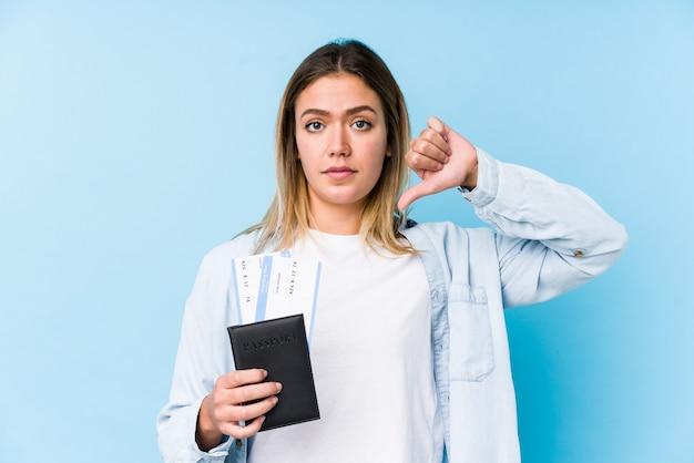 嫌いなジェスチャーを示す分離されたパスポートを保持している若い白人女性は親指を立てます。意見の相違の概念。