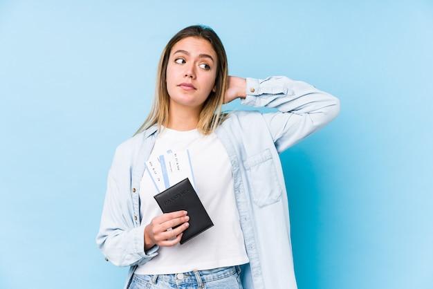 パスポートを保持している若い白人女性は頭の後ろに触れて、考えて、選択を行います。