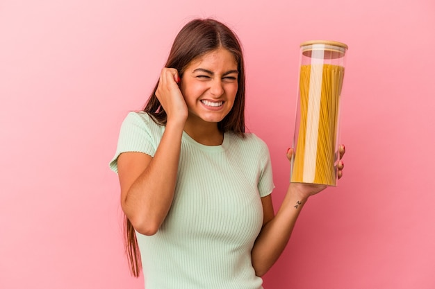 手で耳を覆うピンクの背景に分離されたパスタ瓶を保持している若い白人女性。