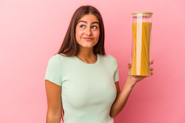 目標と目的を達成することを夢見てピンクの背景に分離されたパスタ瓶を保持している若い白人女性 Premium写真