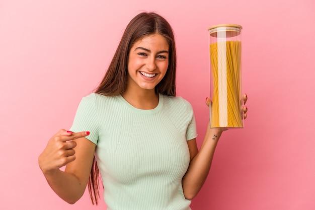 誇りと自信を持って、シャツのコピースペースを手で指しているピンクの背景の人に分離されたパスタの瓶を保持している若い白人女性