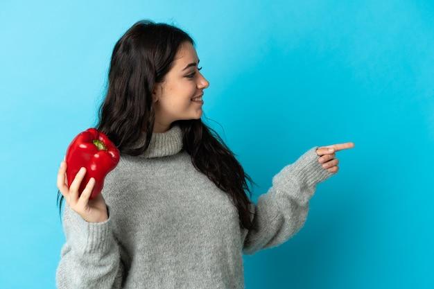 Молодая кавказская женщина держит перец на синей стене, указывая в сторону, чтобы представить продукт