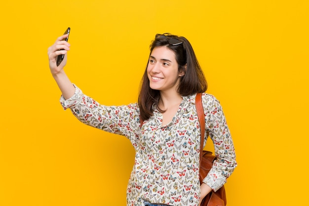 Молодая кавказская женщина, держащая телефон
