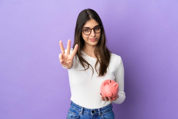 幸せな紫色の背景に分離された貯金箱を保持し、指で3を数える若い白人女性