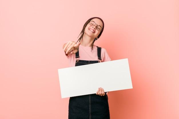正面を向いて陽気な笑顔のプラカードを持っている若い白人女性。