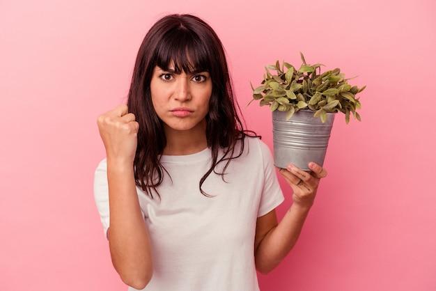 카메라, 공격적인 표정에 주먹을 보여주는 분홍색 벽에 고립 된 식물을 들고 젊은 백인 여자.