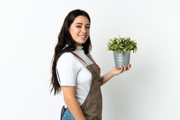 많이 웃 고 흰색 절연 식물을 들고 젊은 백인 여자