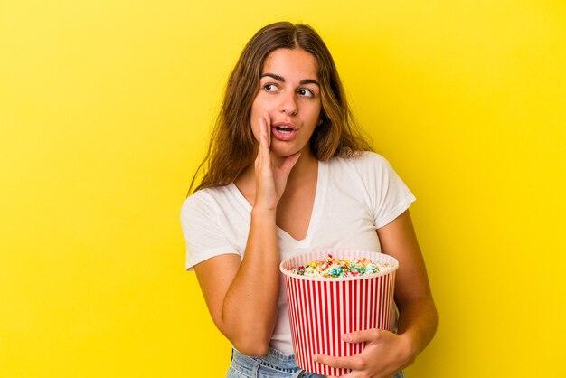 黄色の背景で隔離のポップコーンを保持している若い白人女性は、秘密の熱いブレーキングニュースを言って脇を見ています