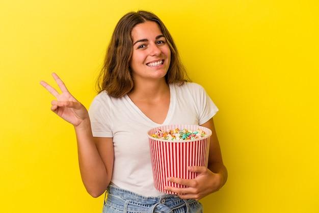 黄色の背景に分離されたポップコーンを持っている若い白人女性は、指で平和のシンボルを示して楽しくてのんきです。