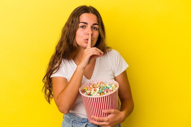 노란색 배경에 격리된 팝콘을 들고 비밀을 유지하거나 침묵을 요구하는 젊은 백인 여성.