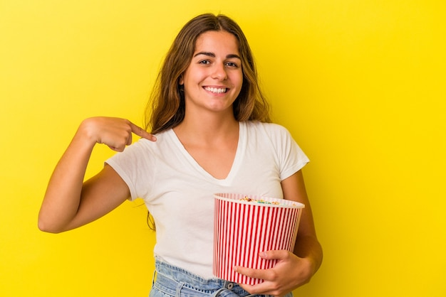 노란색 배경에 격리된 팝콘을 들고 있는 백인 젊은 여성이 셔츠 복사 공간을 손으로 가리키며 자랑스럽고 자신감이 넘칩니다.