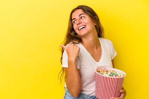 黄色の背景に分離されたポップコーンを持っている若い白人女性は、親指の指を離して、笑ってのんきなポイントを指します。