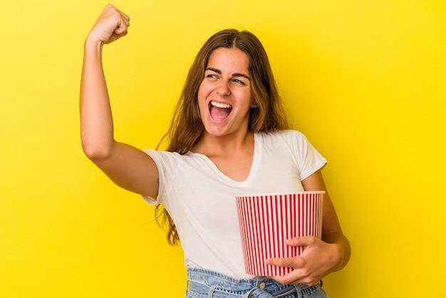 노란색 배경에 격리된 팝콘을 들고 있는 젊은 백인 여성은 승리, 승자 개념으로 주먹을 쥔다.