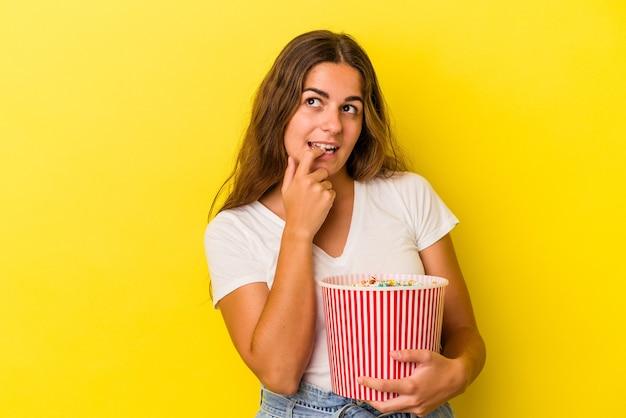노란색 배경에 격리된 팝콘을 들고 있는 백인 젊은 여성은 복사 공간을 보고 있는 무언가에 대해 편안하게 생각했습니다.