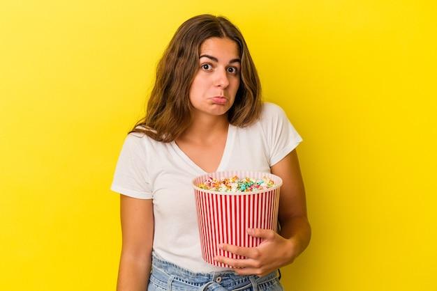 黄色の背景に分離されたポップコーンを保持している若い白人女性は肩をすくめ、目を開けて混乱します。
