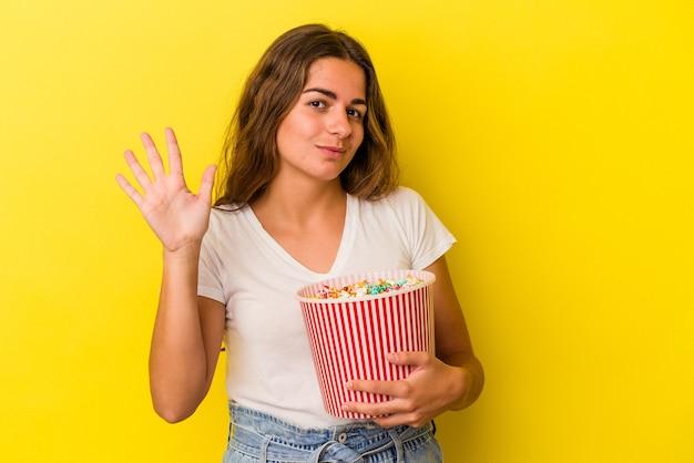 노란색 배경에 격리된 팝콘을 들고 있는 백인 젊은 여성은 손가락으로 5번을 보여주며 밝게 웃고 있습니다.