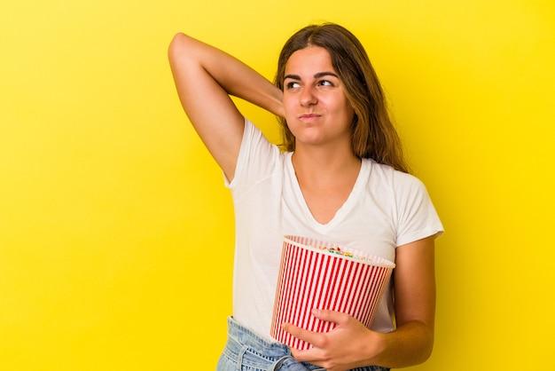 노란색 배경에 격리된 팝콘을 들고 머리 뒤쪽을 만지고 생각하고 선택하는 젊은 백인 여성.