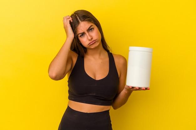 ショックを受けている黄色の背景に分離されたタンパク質ボトルを保持している若い白人女性、彼女は重要な会議を思い出しました。