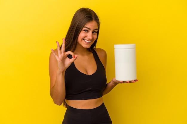 黄色の背景に分離されたタンパク質ボトルを保持している若い白人女性は、陽気で自信を持って大丈夫なジェスチャーを示しています。