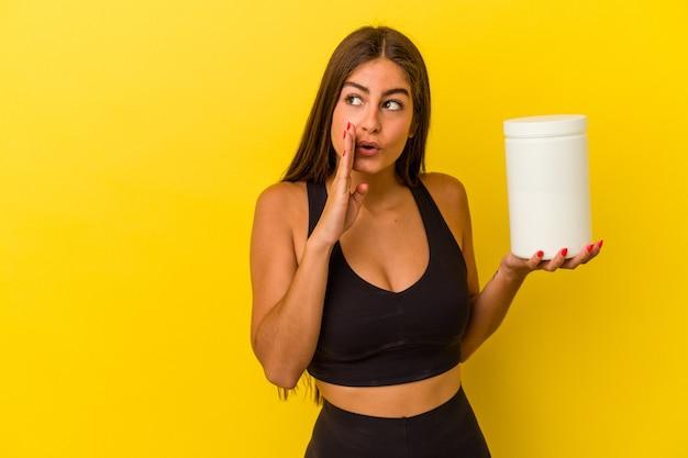 黄色の背景に分離されたタンパク質ボトルを保持している若い白人女性は、秘密のホットブレーキニュースを言って脇を見ています