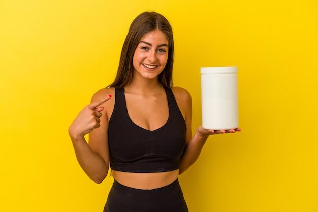 シャツのコピースペースを手で指している黄色の背景の人に分離されたタンパク質ボトルを保持している若い白人女性、誇りと自信を持って