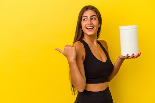 黄色の背景に分離されたプロテインボトルを持っている若い白人女性は、親指の指を離して、笑ってのんきなポイントを指します。